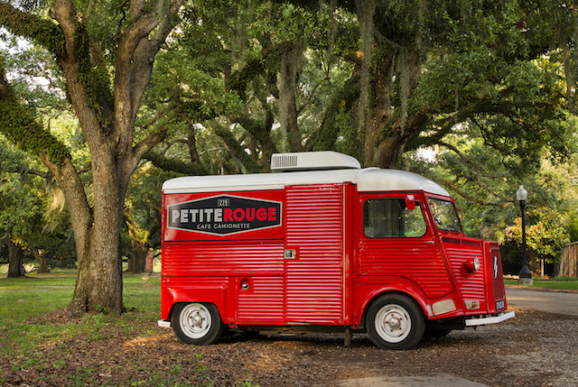 The red Petite Rouge food truck stands shining against Louisiana moss trees.